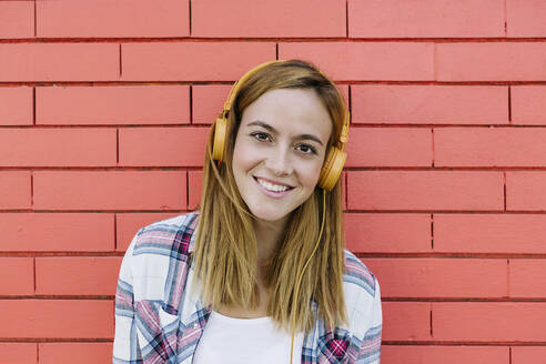 Smiling woman listening to music through headphone against brick wall - XLGF00693