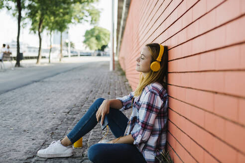 Woman listening music with eyes closed while sitting on footpath against brick wall - XLGF00696