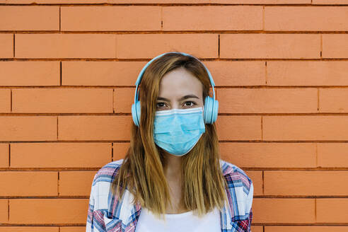 Woman listening music while wearing protective face mask against brick wall - XLGF00699