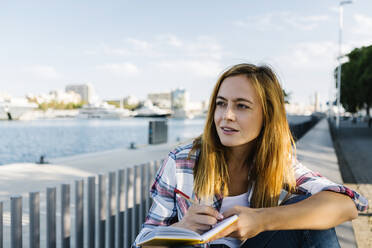 Thoughtful young woman with book sitting on footpath at seaside - XLGF00702