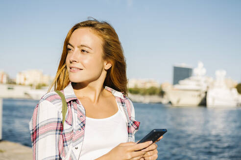 Woman using smart phone looking away while standing at seaside on sunny day - XLGF00705