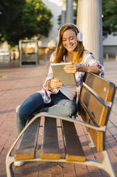 Smiling woman using digital tablet while sitting on bench during sunny day - XLGF00714