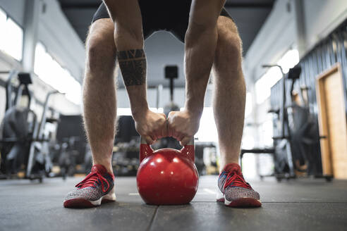 Legs of male athlete holding kettlebell while standing in gym - SNF00727
