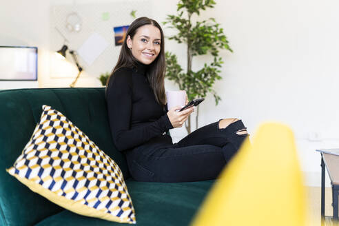 Smiling female blogger holding smart phone and coffee cup while sitting on sofa at loft apartment - GIOF09417