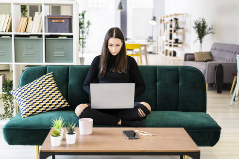 Beautiful young woman using laptop for blogging while sitting on sofa at loft apartment - GIOF09423