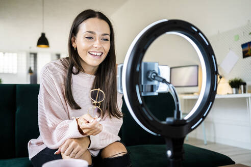Smiling beautiful female vlogger filming through smart phone at home - GIOF09456
