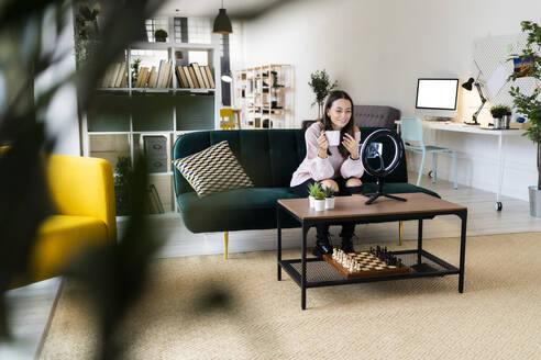 Smiling female influencer vlogging through smart phone and lighting equipment on coffee table at loft apartment - GIOF09459