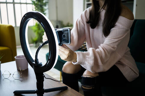 Young female influencer sitting on sofa while adjusting smart phone on lighting equipment for vlogging at loft apartment - GIOF09465