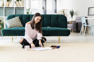 Smiling beautiful young woman sitting with note pads and coffee cup on carpet against sofa at home - GIOF09471