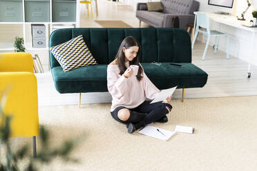 Beautiful young woman drinking coffee while reading paper by note pads on carpet against sofa at home - GIOF09474