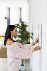 Young woman adjusting mirror on white wall at home - GIOF09480