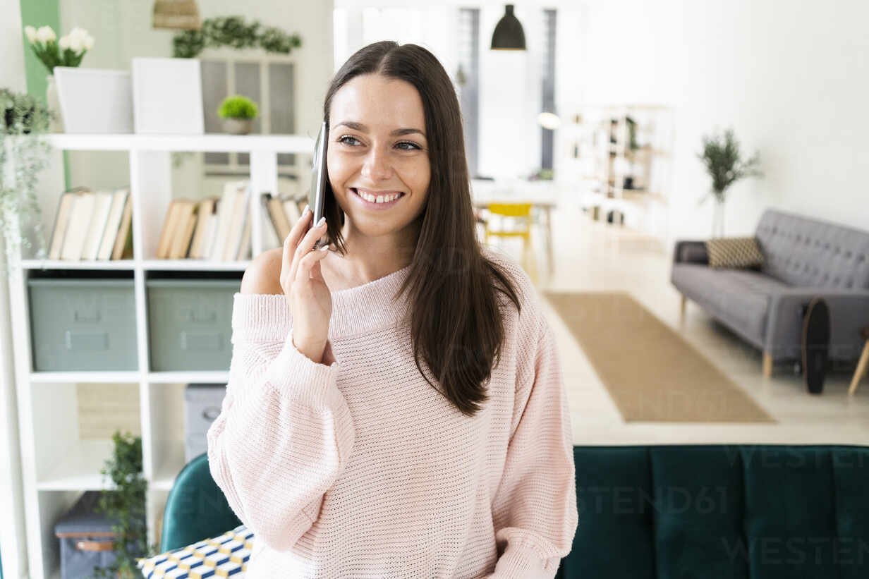 Smiling beautiful woman talking on mobile phone while standing in living room at loft apartment - GIOF09483 - Giorgio Fochesato/Westend61