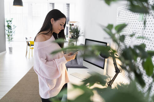 Beautiful young female blogger using mobile phone while standing at computer desk in loft apartment - GIOF09486