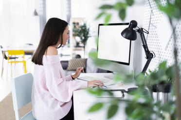 Young female blogger using computer at desk in loft apartment - GIOF09489