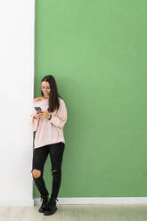 Beautiful young woman using mobile phone while standing against green wall - GIOF09495