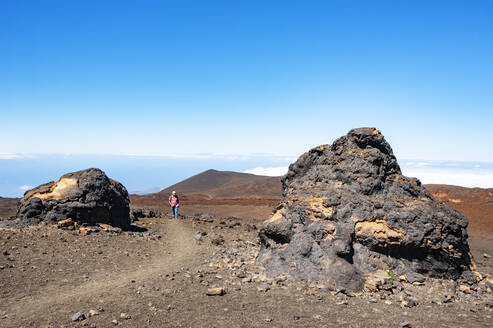 Senior man hiking along trail stretching across brown barren landscape of Tenerife island - WWF05557