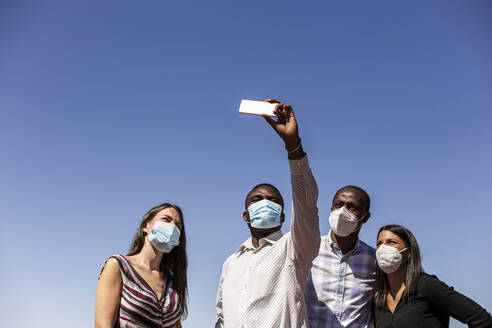 Business professionals taking selfie with protective face masks against clear blue sky on sunny day - LJF01792