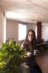 Smiling young female entrepreneur having coffee during office break - LJF01798
