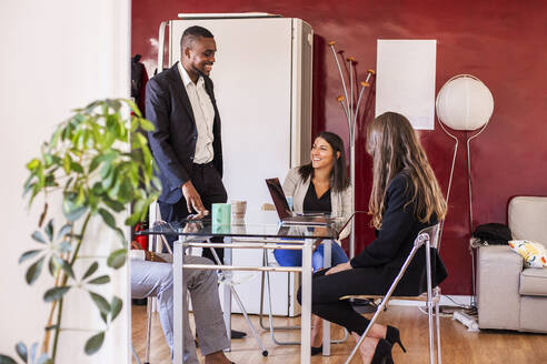 Smiling businessman discussing with colleagues in coworking office - LJF01816