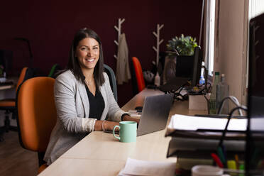 Smiling businesswoman with laptop at desk in office - LJF01819
