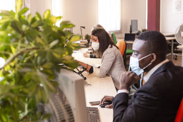Female business professional in protective face mask working with colleagues at desk in coworking office during COVID-19 - LJF01834