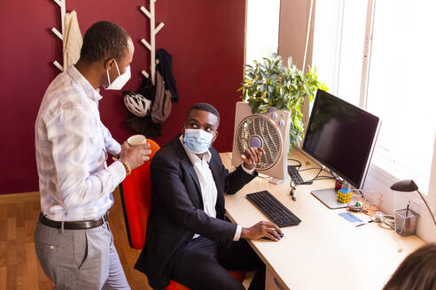Businessmen in protective face masks discussing at desk in coworking office during COVID-19 - LJF01837