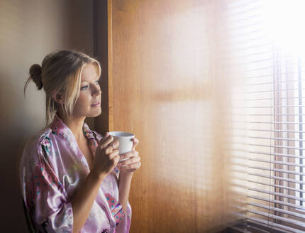 Thoughtful young woman in bathrobe looking through window while having coffee at home - AJOF00482