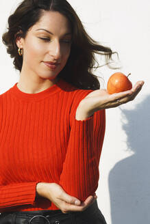 Beautiful woman holding apple while standing against wall on sunny day - NGF00686