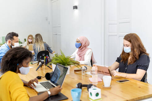 Business people wearing face mask while working at office - MPPF01180