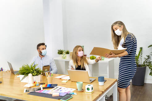 Employee wearing face mask discussing file while working with coworker at office - MPPF01201