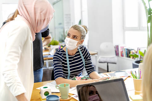 Coworker wearing face mask discussing while using mobile phone at office - MPPF01222