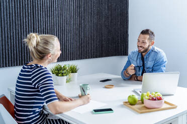 Smiling man and woman drinking coffee while sitting at office - MPPF01231