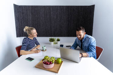 Female and male coworker discussing while working on laptop at office - MPPF01234