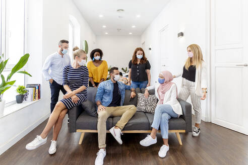 Male and female employee wearing face mask sitting and standing by sofa at office - MPPF01237