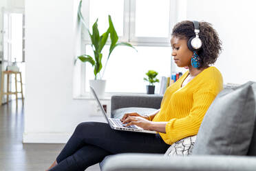 Young woman wearing headphones using laptop while sitting on sofa at office - MPPF01243