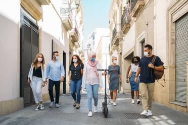 Friends wearing face masks walking on street in city - MPPF01246