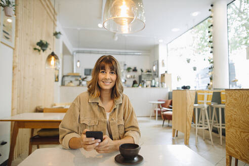 Businesswoman using smart phone while sitting in cafe - GUSF04551