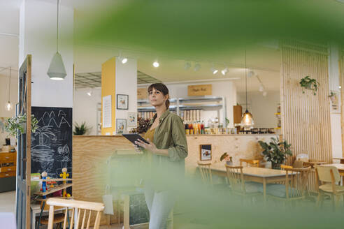 Businesswoman holding digital tablet looking away while standing in cafe - GUSF04554