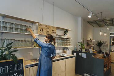 Female owner arranging glass jars on shelf in cafe - GUSF04569