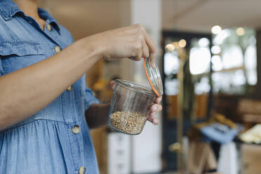 Midsection of female owner opening food jar while standing in cafe - GUSF04572