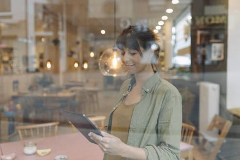 Female owner using digital tablet seen through window standing in coffee shop - GUSF04587