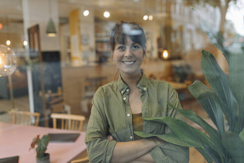 Smiling businesswoman with arms crossed looking through window standing in cafe - GUSF04590