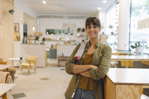 Female owner with arms crossed napkin on shoulder standing in coffee shop - GUSF04593