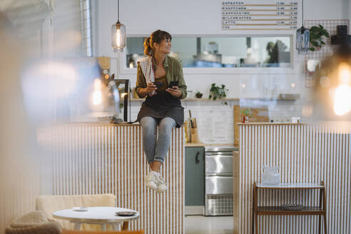 Young businesswoman holding coffee looking away using smart phone sitting on counter in cafe - GUSF04599