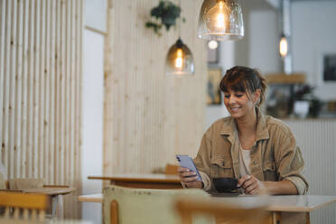 Smiling female owner text messaging on smart phone holding coffee cup sitting in cafe - GUSF04611