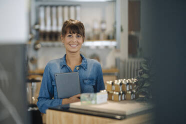 Happy female owner holding digital tablet standing in coffee shop - GUSF04620