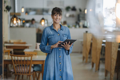 Smiling female entrepreneur using digital tablet while standing in coffee shop - GUSF04623