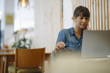 Female owner concentrating while using laptop sitting in cafe - GUSF04641