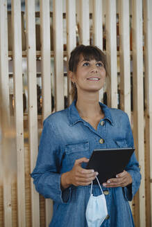 Female entrepreneur holding digital tablet and protective face mask looking up while standing in cafe - GUSF04650