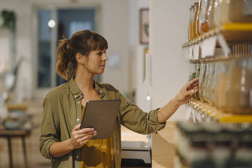 Female owner examining while holding digital tablet in coffee shop - GUSF04674
